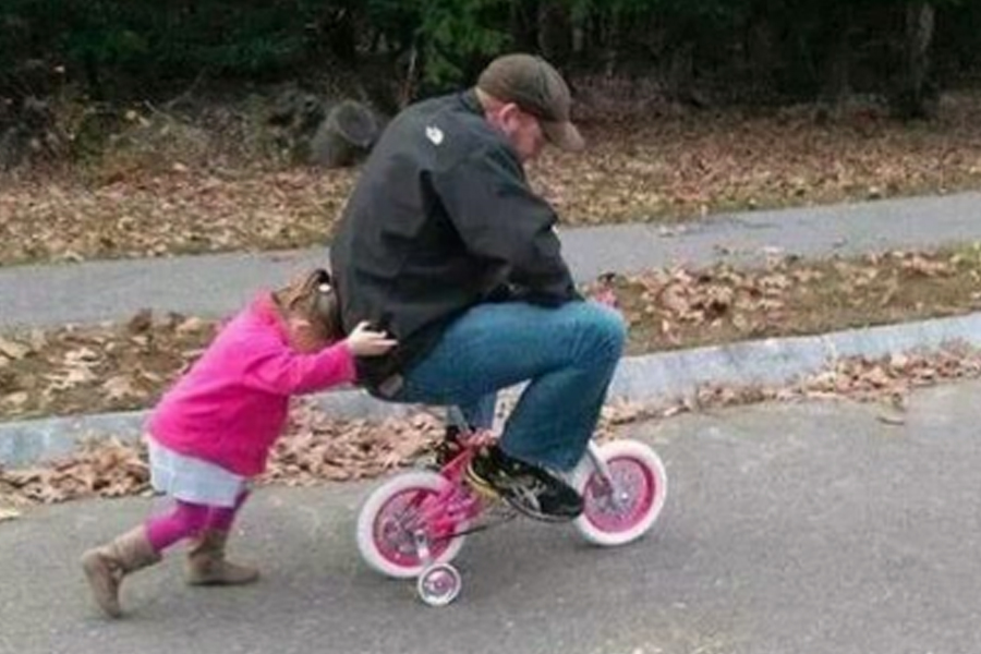 dad riding daughters bike