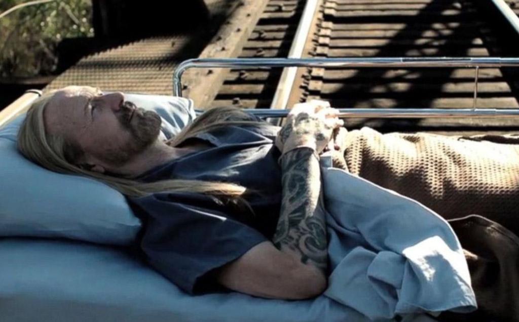 William Hurt laying on train tracks
