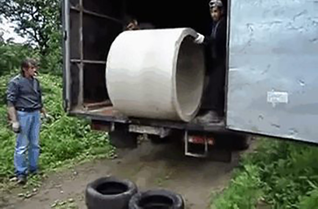pushing a concrete pipe out of a truck