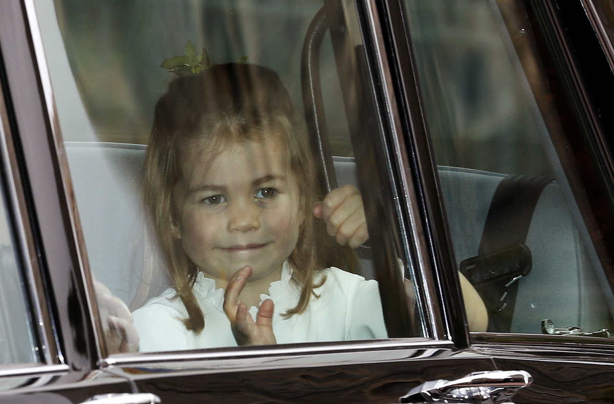 Princess Charlotte waves as she arrives by car for the wedding of Princess Eugenie of York and Jack Brooksbank