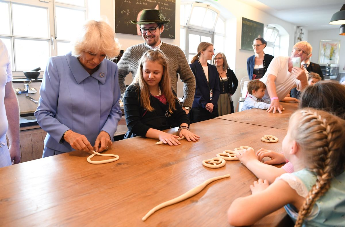 Britain's Camilla, Duchess of Cornwall shapes a bretzel with pastry as she meets with young women during her visit to the IMMA shelter for young women
