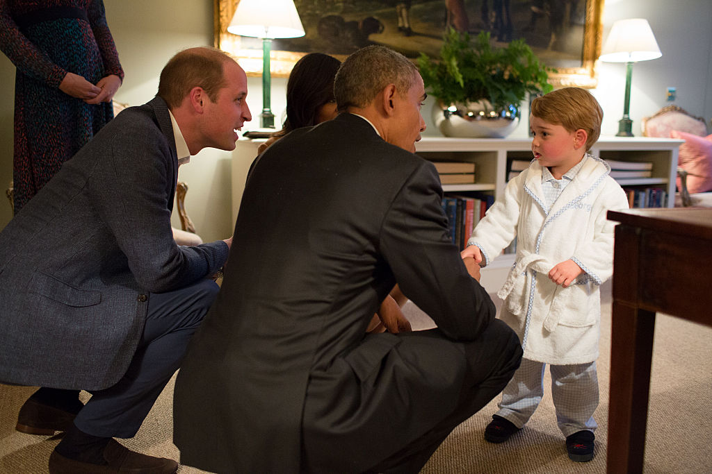 In this handout provided by The White House, President Barack Obama, Prince William, Duke of Cambridge and First Lady Michelle Obama talks with Prince George at Kensington Palace