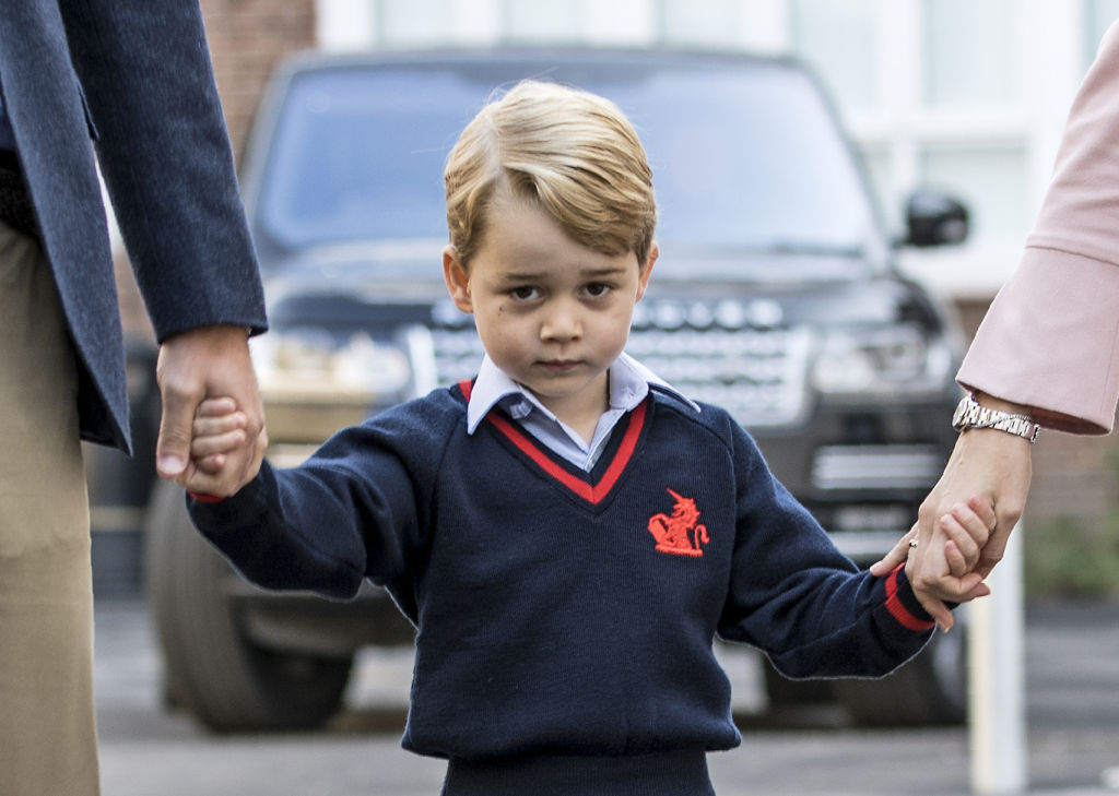 Britain's Prince George (C) accompanied by Britain's Prince William (L), Duke of Cambridge arrives for his first day of school at Thomas's school