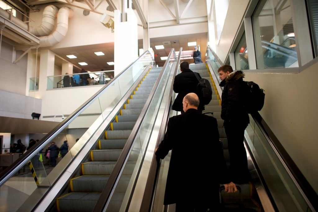 Travelers ascend an escalator to a long security line
