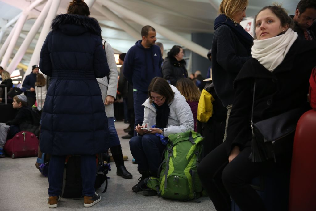 jfk passengers sit on their luggage