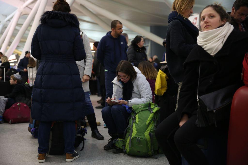 jfk passengers sit on their luggage
