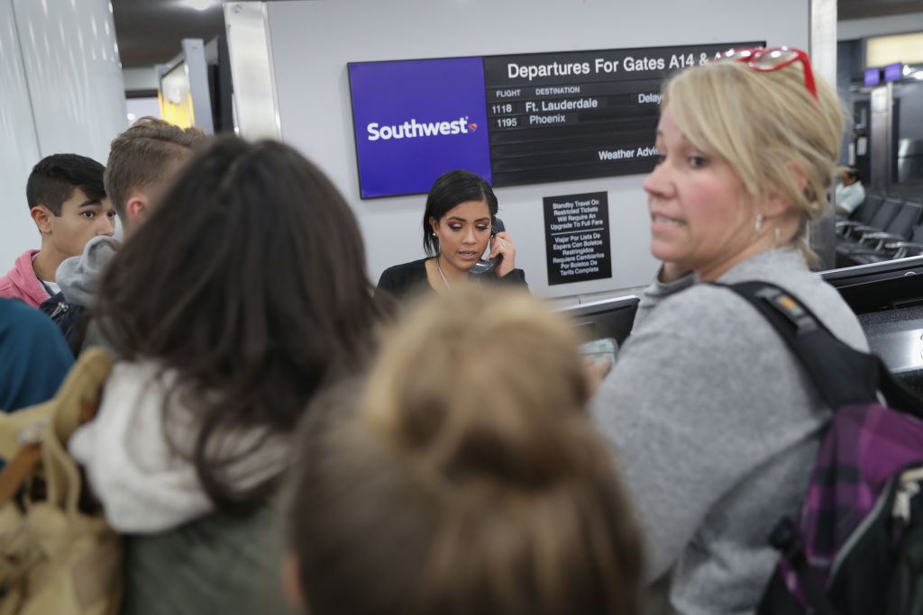 Passengers wait to rebook after their flights were cancelled due to a snow storm