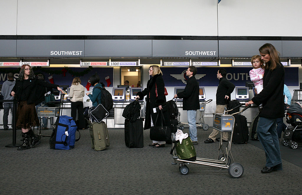 passengers wait in line to check into flights at San Francisco International Airport