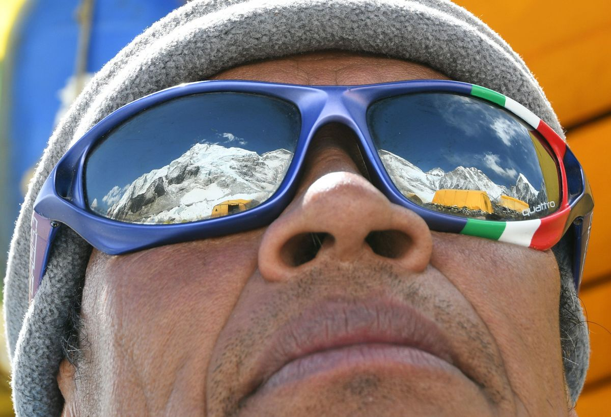 Mount Everest is reflected in a man's sunglasses