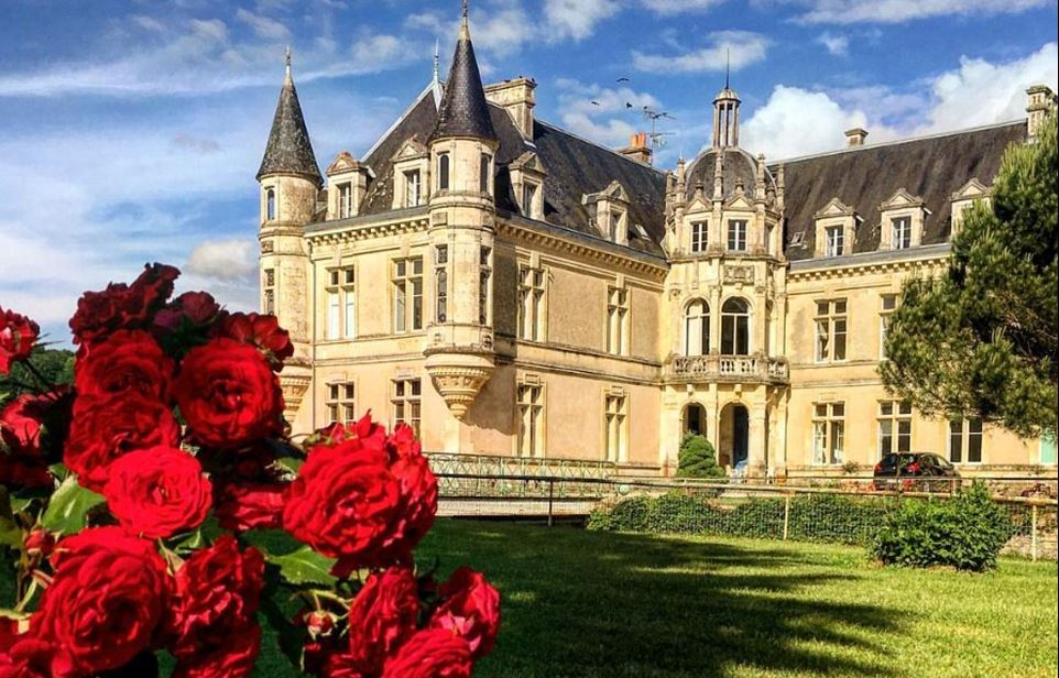 Picture of the Cheateau de Bourneau behind red roses