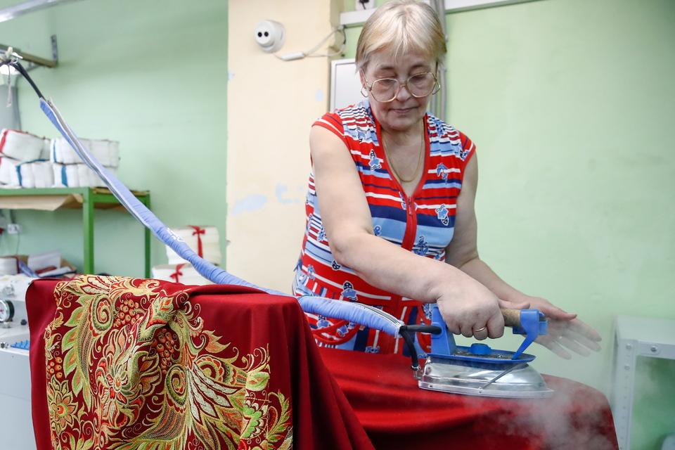 A worker ironing an embroidered shawl at the Torzhokskiye Zolotoshvei goldwork embroidery factory