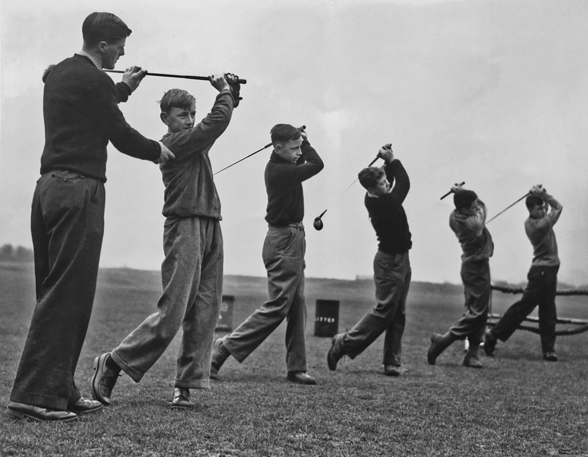 Five young men being taught how to play golf by an instructor circa 1950.