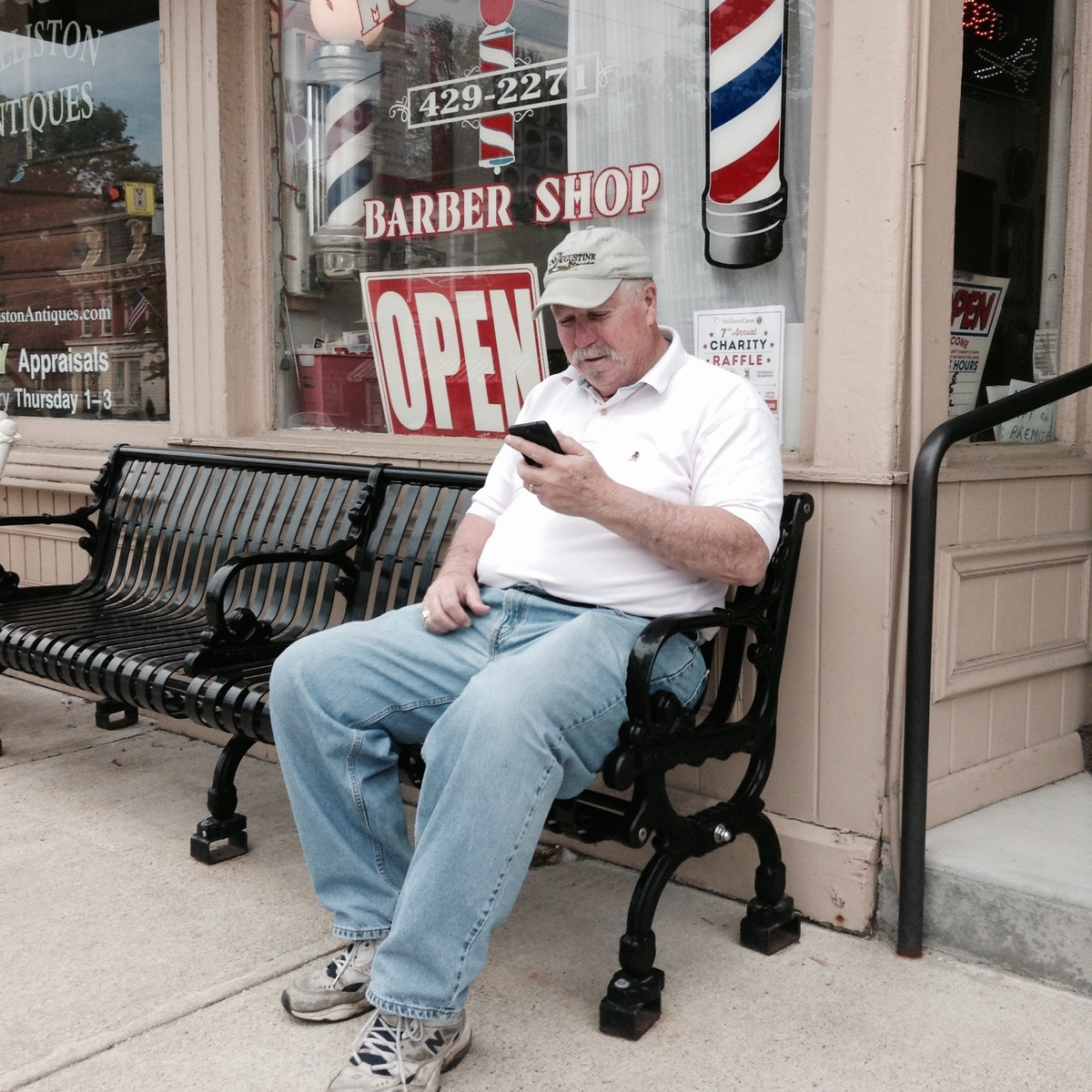 Man on a Cellphone Outside a Barbershop in Holliston, MA