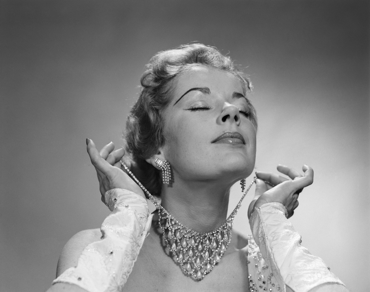 1950s GLAMOROUS WOMAN EYES CLOSED CHIN LIFTED PUTTING ON ELABORATE DIAMOND RHINESTONE NECKLACE