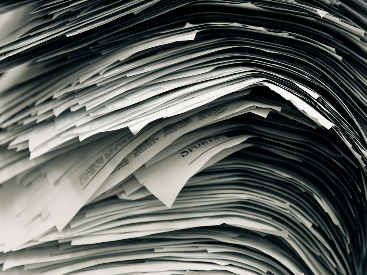 A stack of newspaper proofs piled on an empty desk