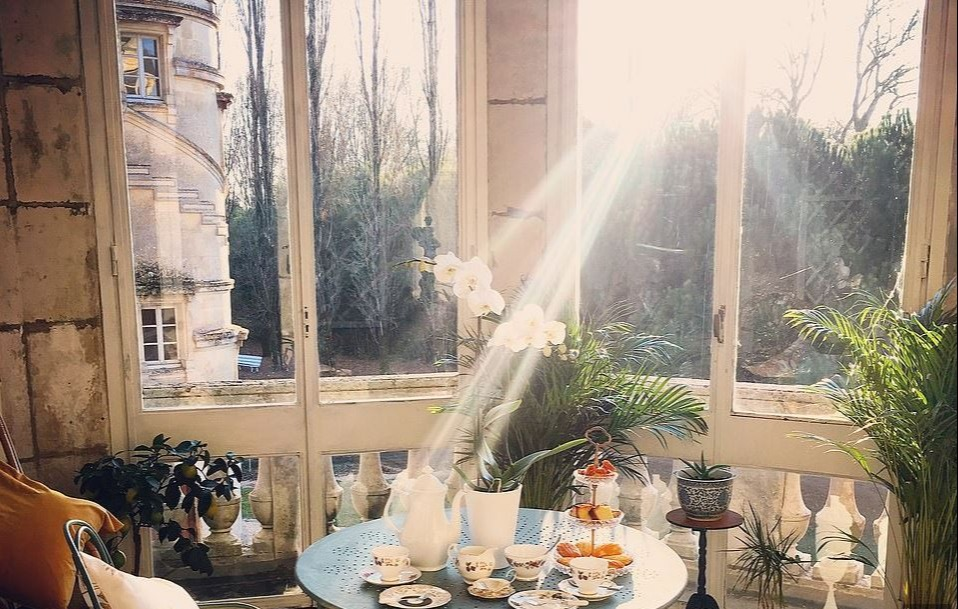 Solarium in the Chateau de Bourneau with sunrays descending upon chairs and a tea set