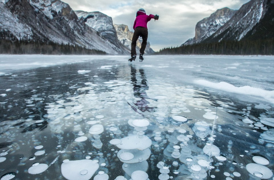 ice skater on a methane bubble lake in Canada