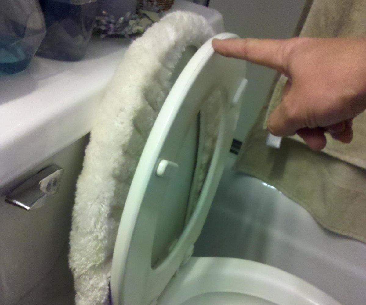 man lifting up toilet seat cover