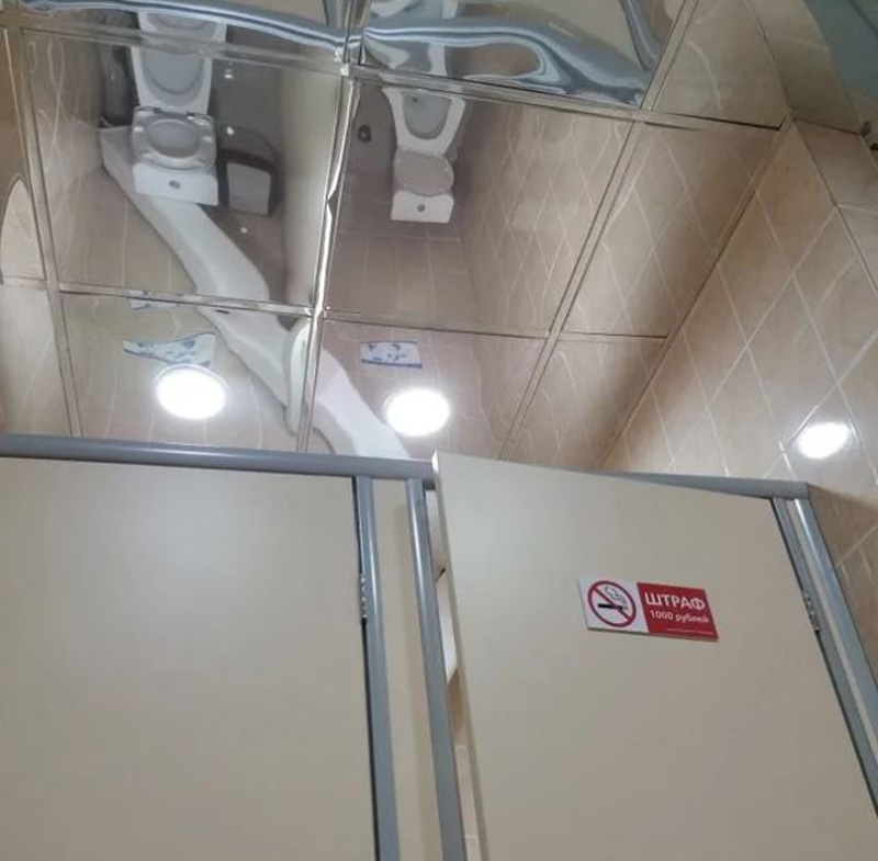 bathroom with mirrored ceiling allowing you to see whoever is in the stall