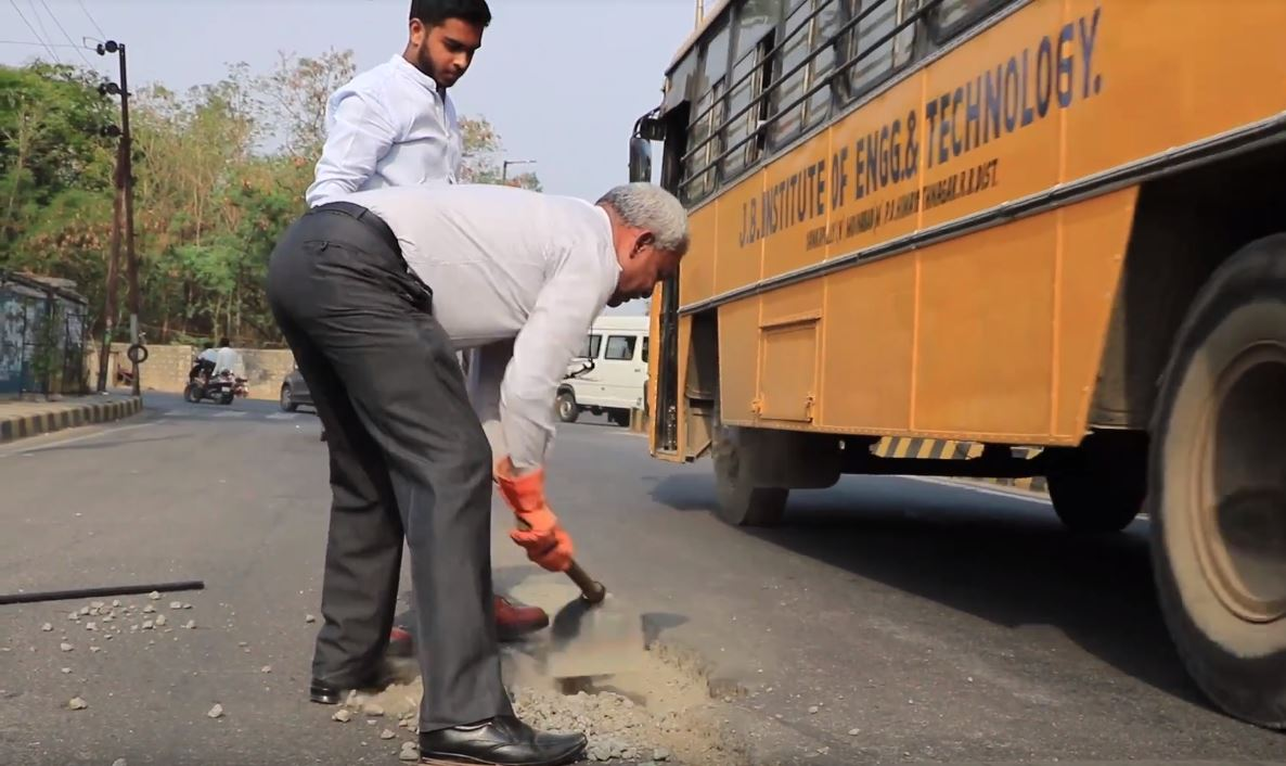 Gangadhara Tilak Katnam and a volunteer repairing a pothole in India