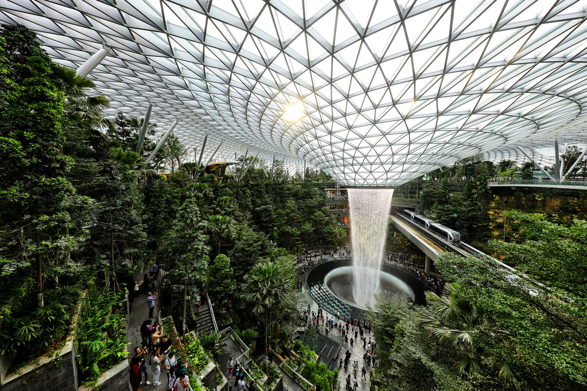 The skytrain rides past the Rain Vortex at the Jewel Changi Airport on April 11, 2019 in Singapore. Officially opening on April 17, Singapore's Changi Airport Jewel includes a 40-meter indoor waterfall contained under a steel-and-glass dome reportedly built for SGD 1.7 billion.