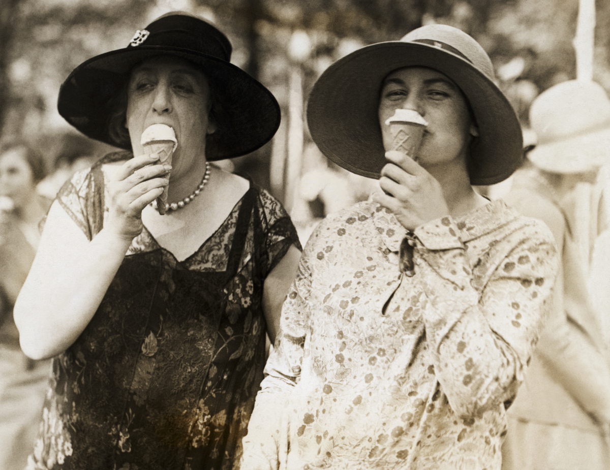 Madame Charalambos Simopoulos, wife the Minister of Greece to the United States, left, and Miss Suzette Dewey, daughter of the assistant secretary of the treasury, right, were caught in this informal pose while eating uce cream at the annual charity fete at the National Capital.