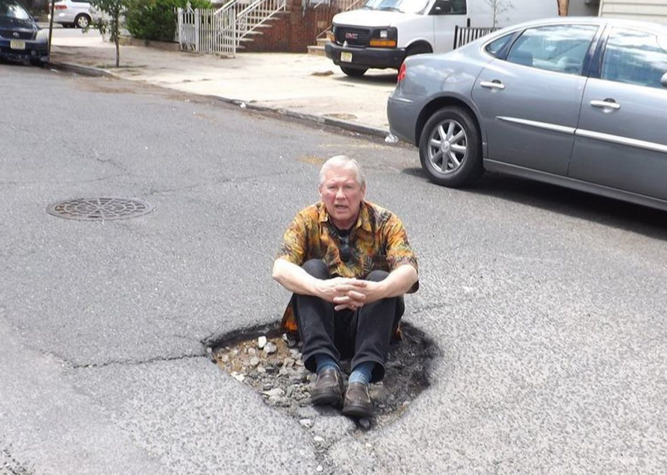 Jersey man sits in a pothole to call attention to it