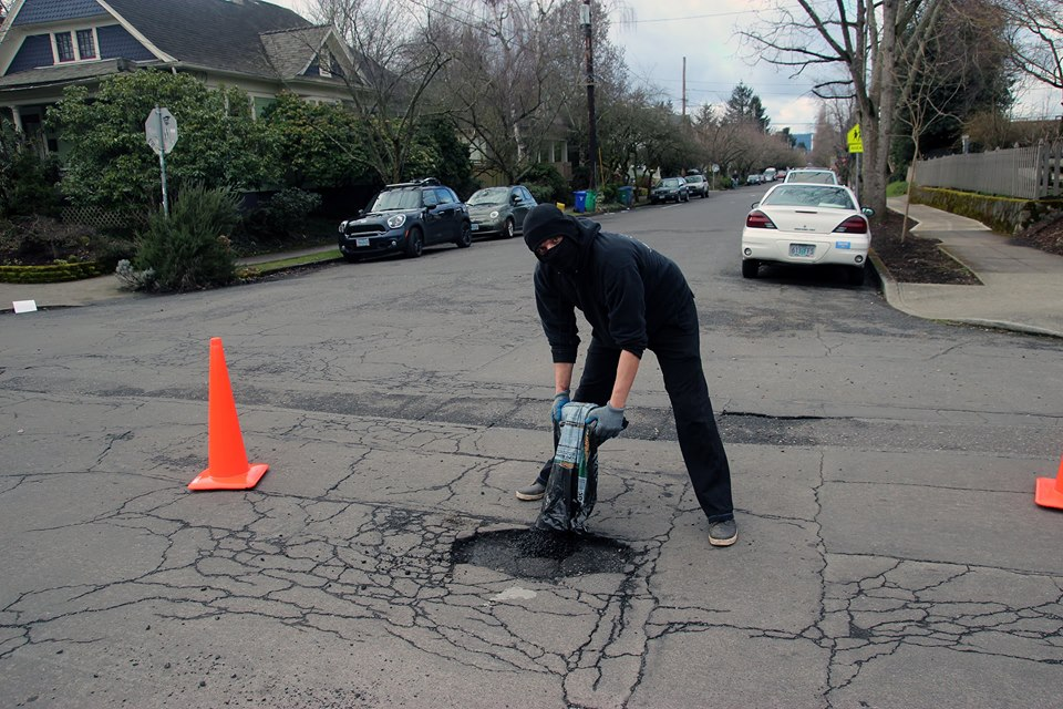 Portland Anarchist Road Care member fills in a pothole in Oregon