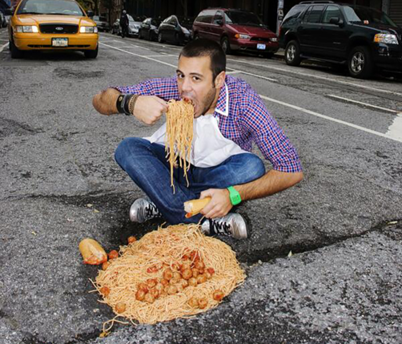 man eating spaghetti out of a pothole in New York City