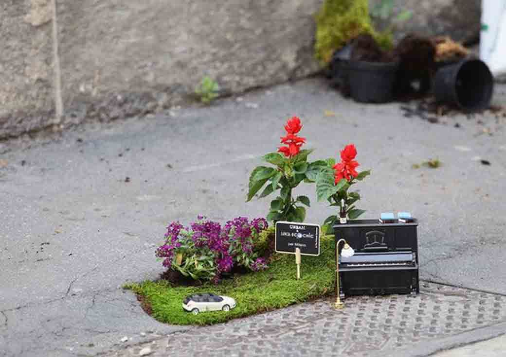 Steve Wheen's garden art in a pothole featuring a miniature car, sign, and piano