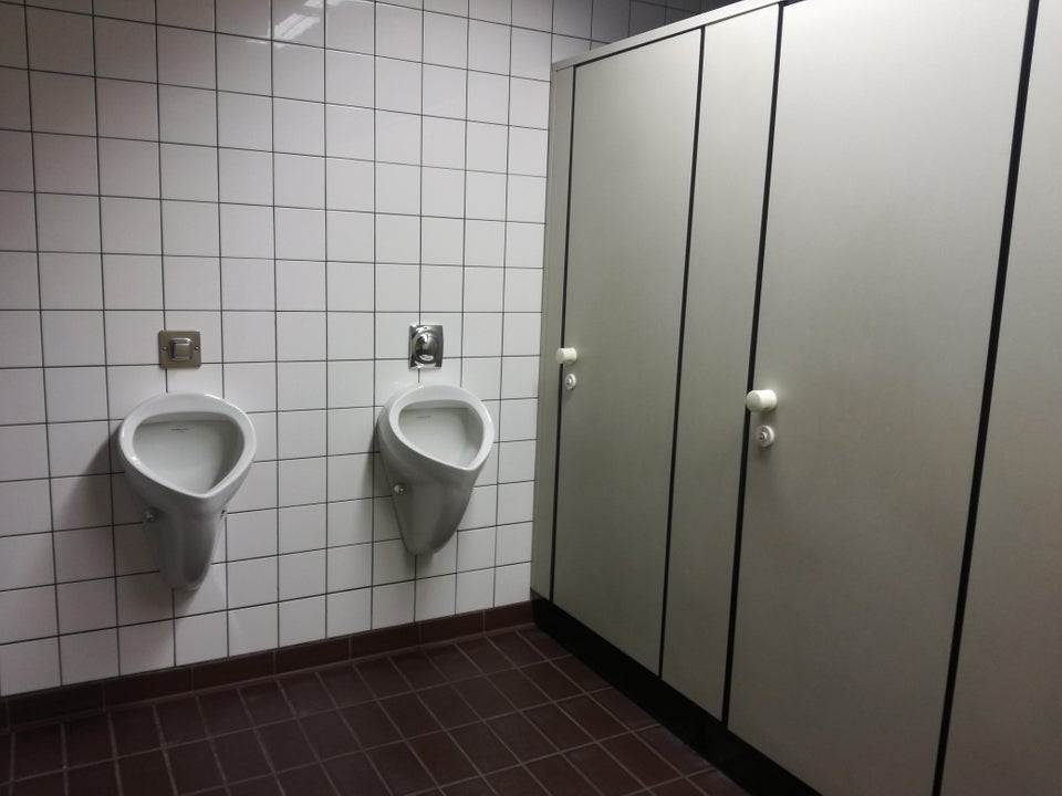 toilet urinals right in front of the bathroom stall