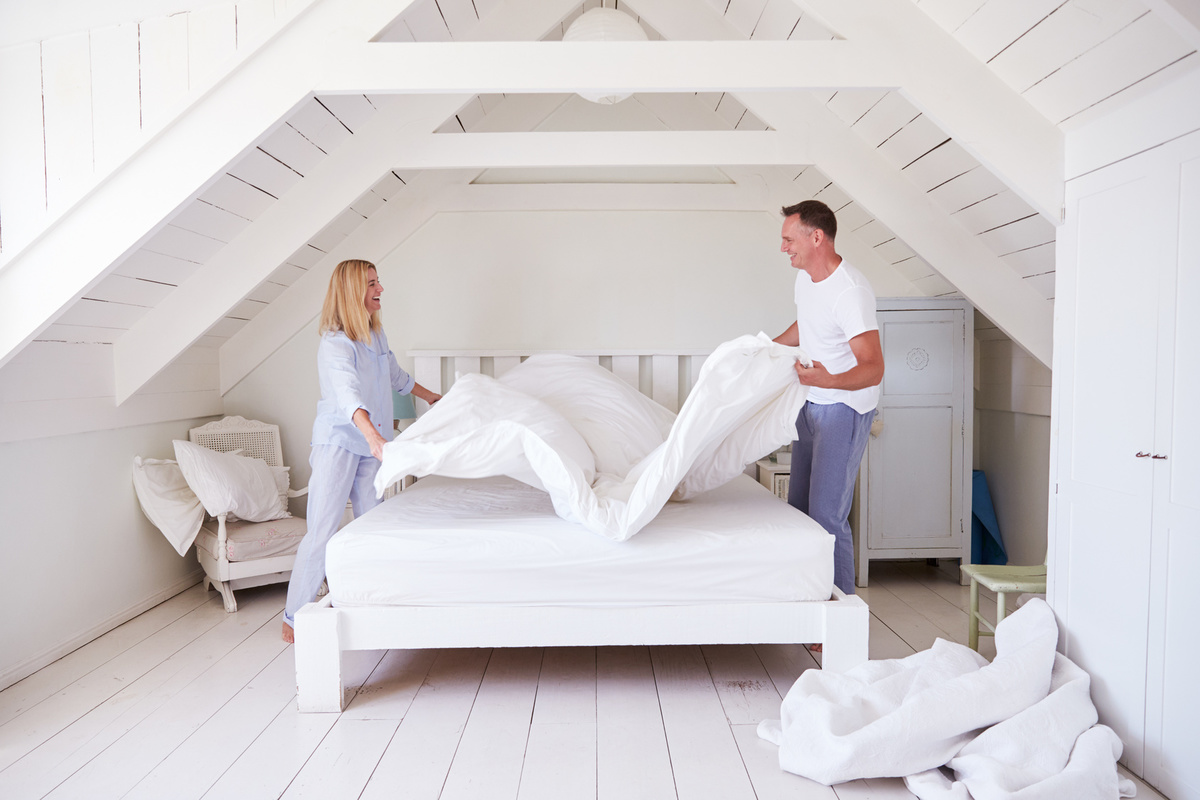 a couple making the bed together