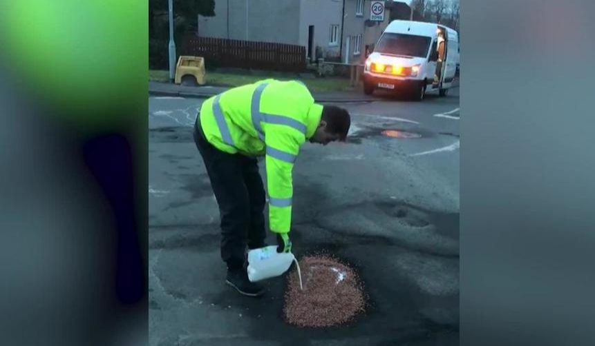 man pretending to be a road worker filling a pothole with coco pops and milk