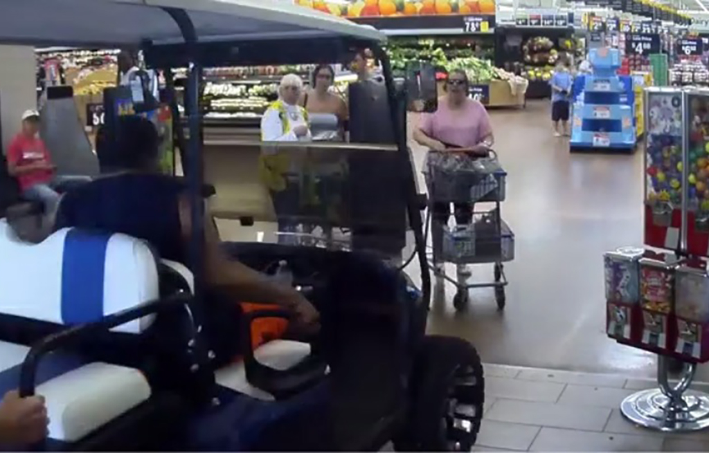 Man driving golf cart through Walmart