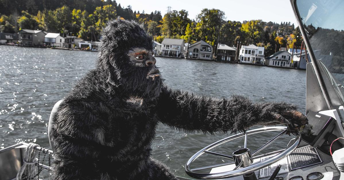 bigfoot driving a boat in a lake