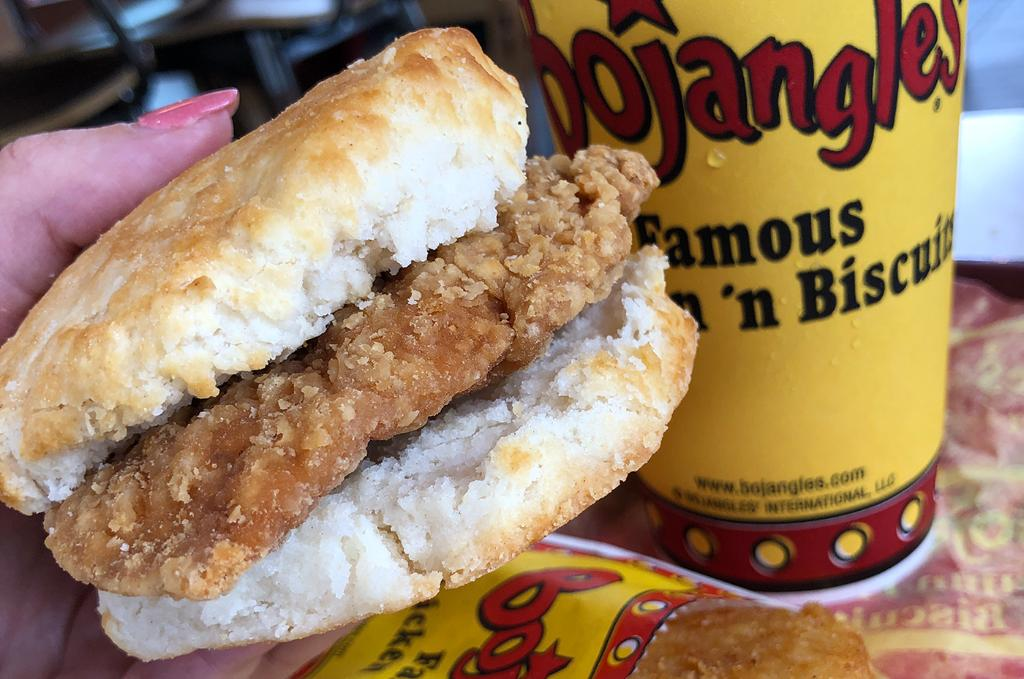 man holds Bojangles chicken biscuit with a drink in the background