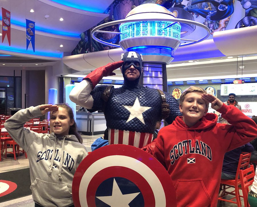 Captain America actor posing with kids at the Marvel Character Cafe