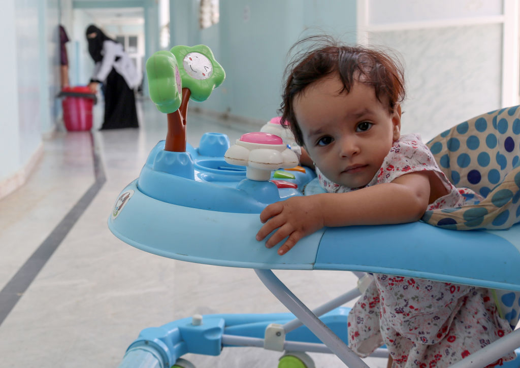 A female toddler looks at the camera while sitting in her babywalker