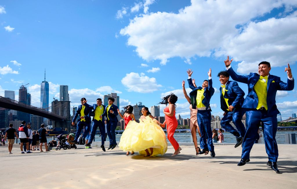 A colorful wedding party poses midair as they jump for a photo.