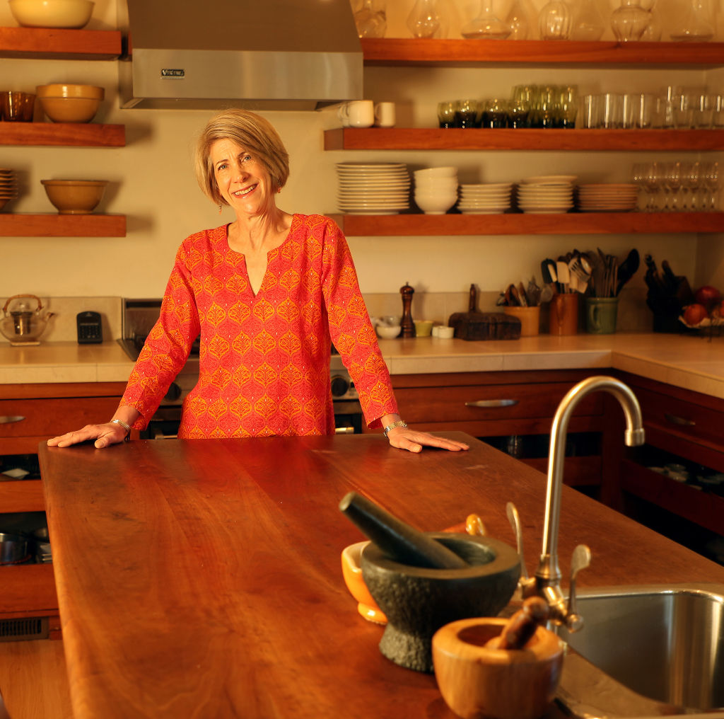 A woman stands in front of a large island in her wooden kitchen