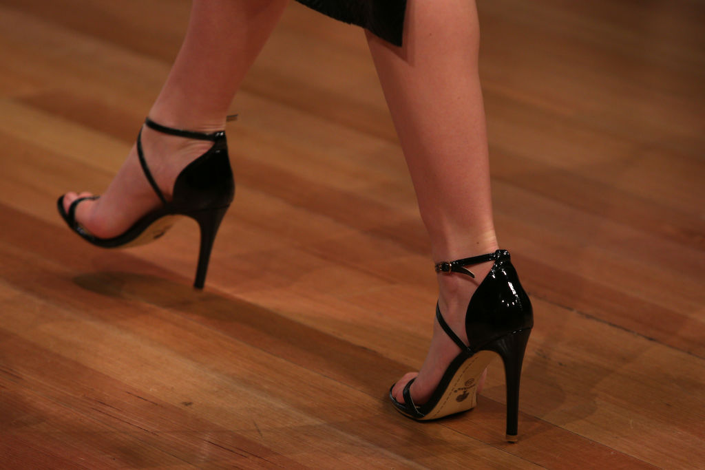 A woman's feet are photographed as she struts on wooden floors in glossy black heels.
