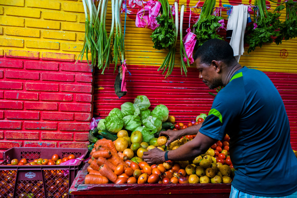 A man picks fruit from and fruit and vegetables stand
