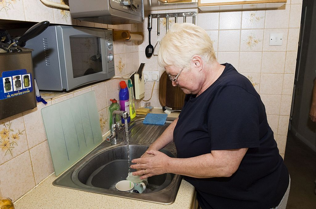 An older woman cleans mugs in her sink.