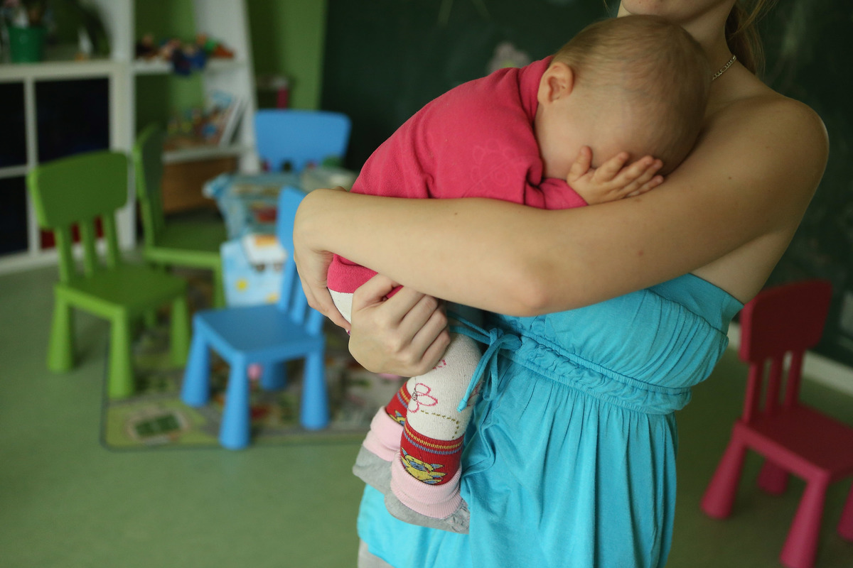 Single mother Nancy Kett, 19, cradles her 11-month-old daughter Lucy in the playroom of the