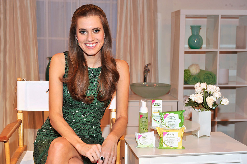 A skin spokeswoman smiles for the camera alongside the products she's selling