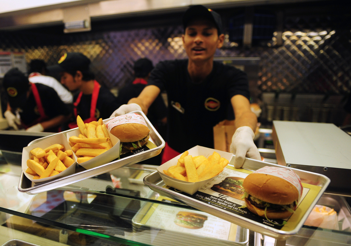 Pakistani Fatburger employee serves burgers to a customer at an outlet in Karachi.