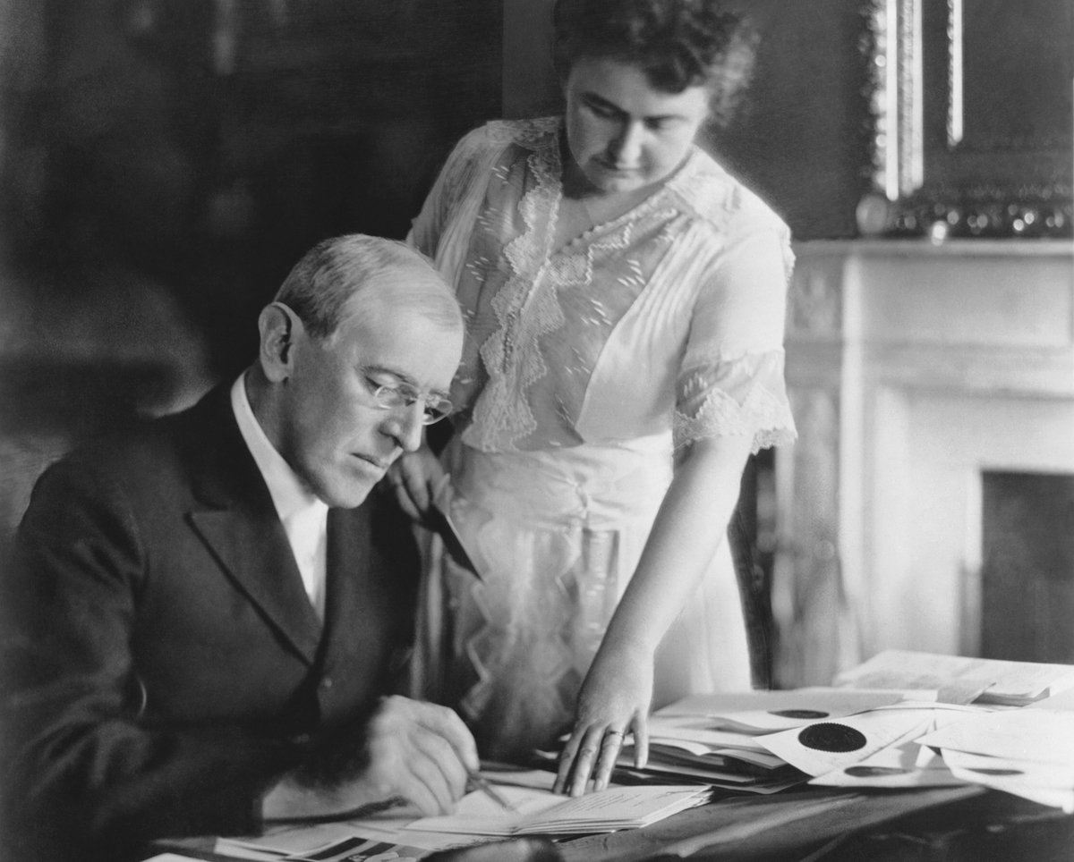 First Lady Edith Wilson assists President Woodrow Wilson at his desk in the White House, 1920