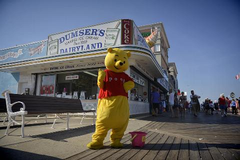 A Winnie The Pooh impersonater poses on the boardwalk.