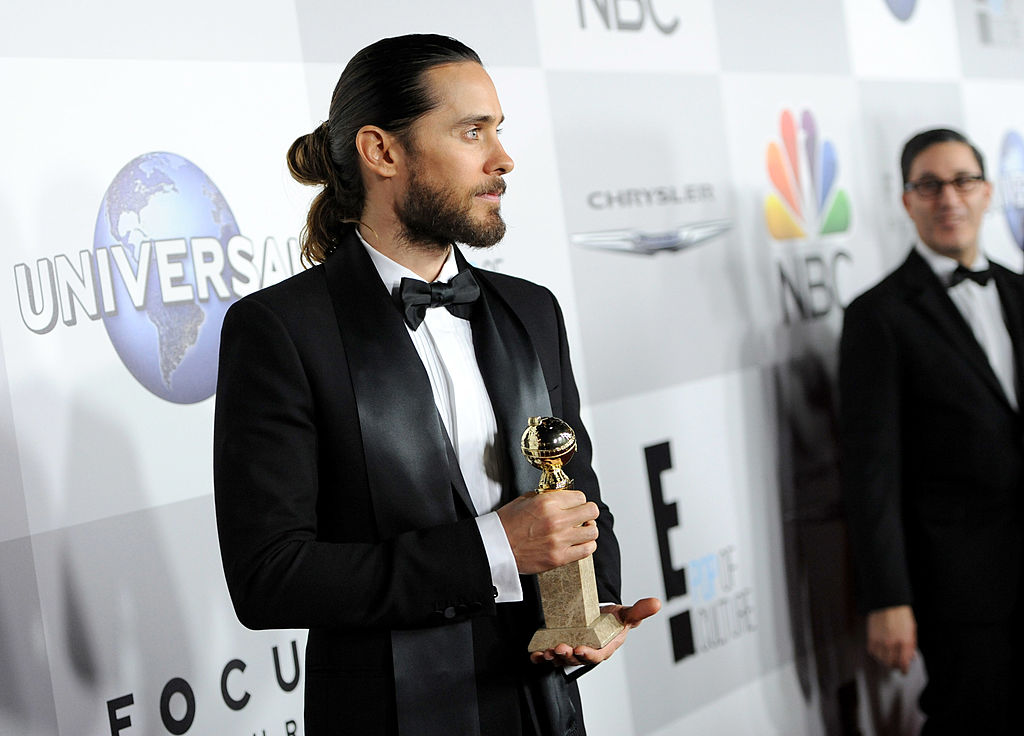 An actor and musician holds an award sporting a tuxedo and a man-bun.