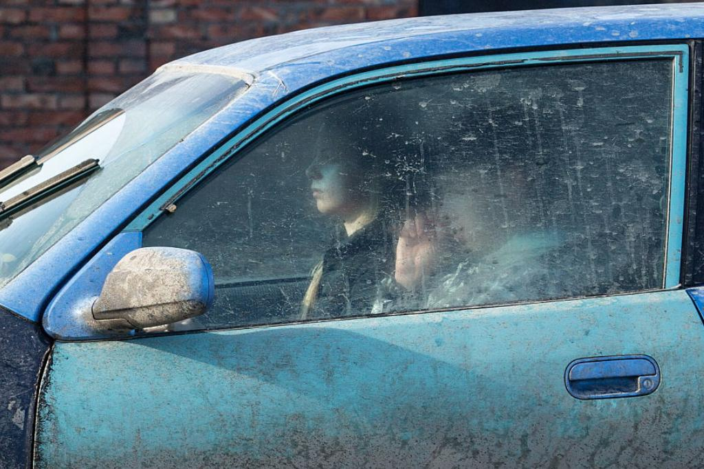 Two people ride in a car that is covered in dirt.